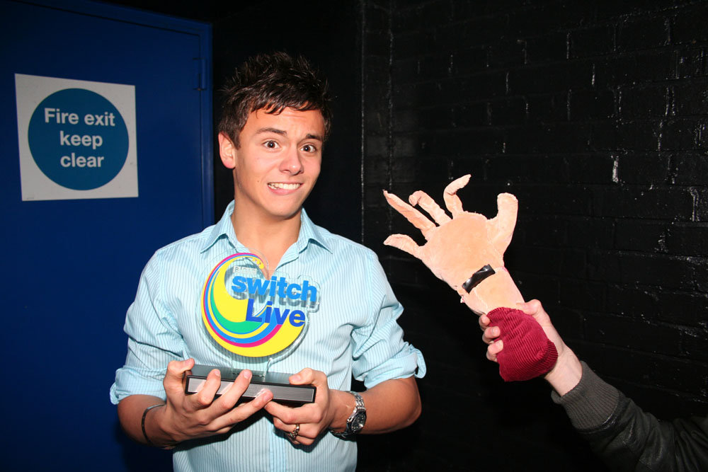Tom Daley with his award... and a fake hand. Why not?