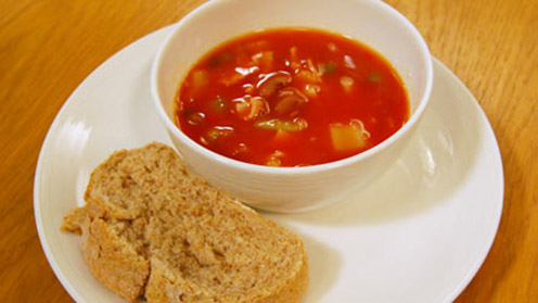 Bowl of baked bean soup with roll