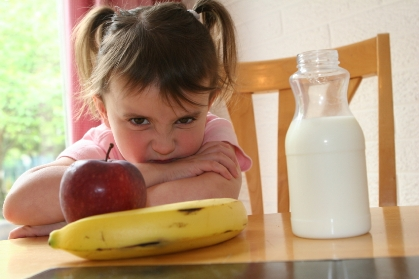 Girl staring at apple and banana with milk bottle