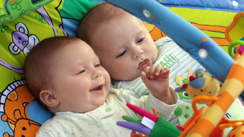 Two babies; one playing with hanging mobile