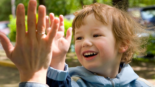 A picture of a child giving a high-five.