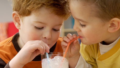 Two boys blowing bubbles in drink through straw