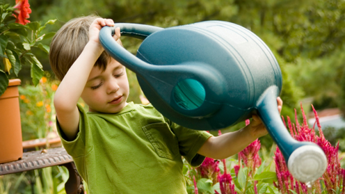 Boy using watering can outdoors