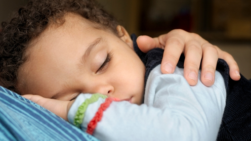 Child sleeping with parents hand comforting him