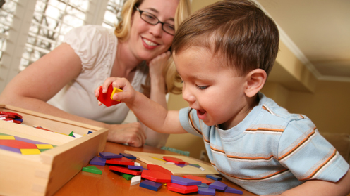Woman smiling as child plays with shapes