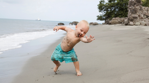 Baby playing on beach with sand on face