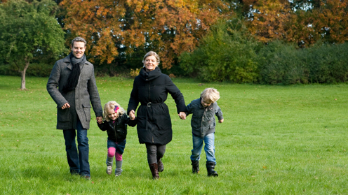 Man, woman and two children walking outdoors