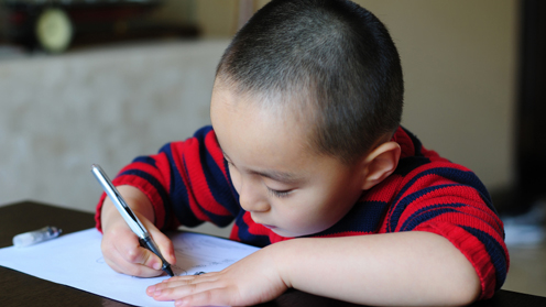 child with pen and paper