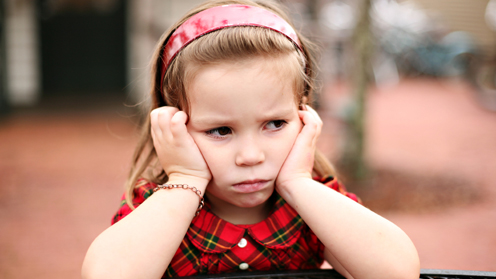 Girl with hands on cheeks, looking upset