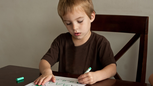 Boy colouring and writing