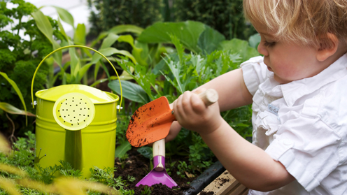Child using gardening equipment in soil