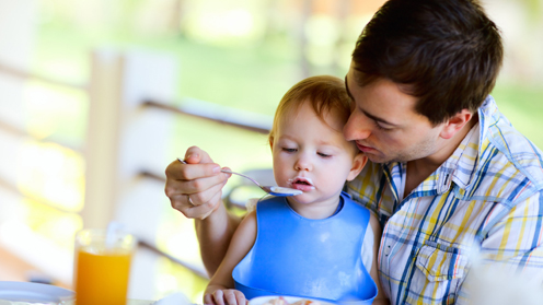 Man feeding child