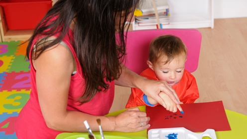 Child finger painting with woman