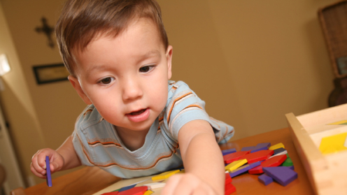 toddler with puzzle toy