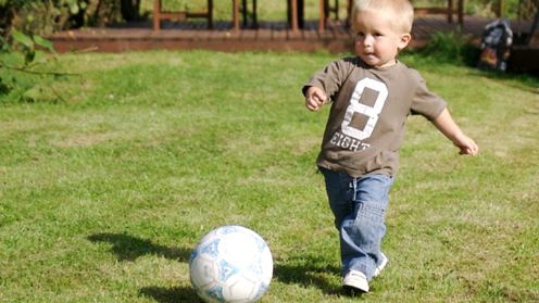 Boy kicking football