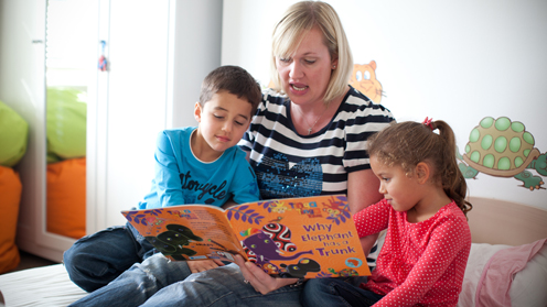 Children reading a book with an adult