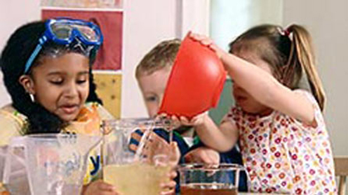Children pouring liquid into a bowl