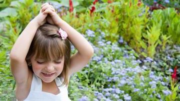 Girl raised hands near flowers