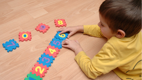 Woman with girl arranging number toys