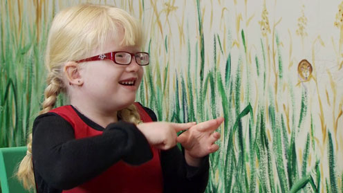 A child demonstrating a Makaton sign