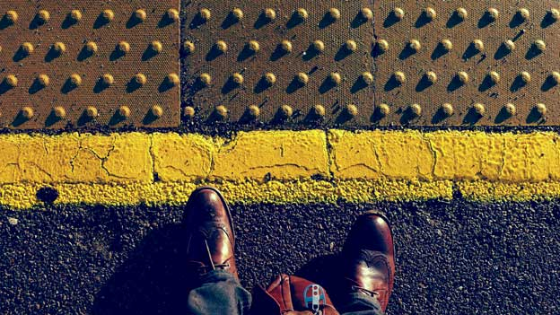 Image of man's feet on train platform