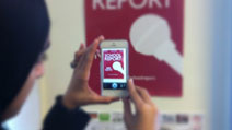 A student looking at the School Report logo on her smartphone.