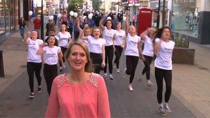 A singer perforoming in the Licoln Lip Dub, followed by dancers and performers