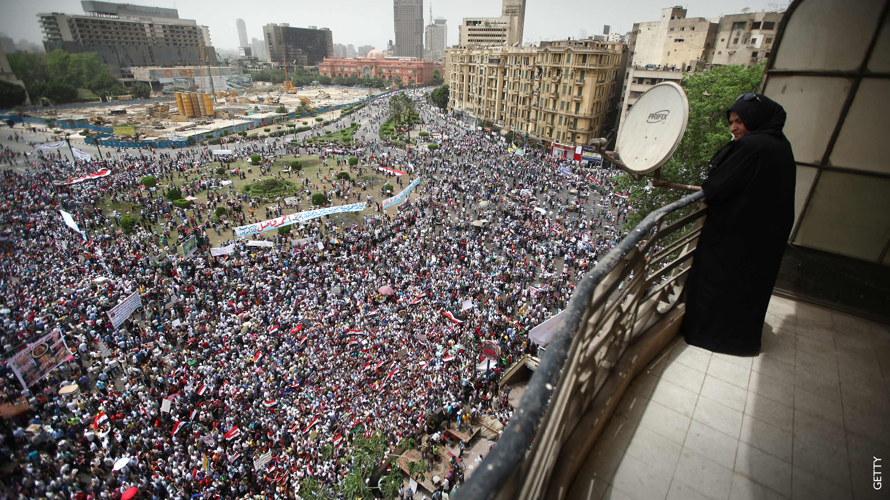 A woman on a balcony overlooks a crowd in Tahrir Square, Cairo.